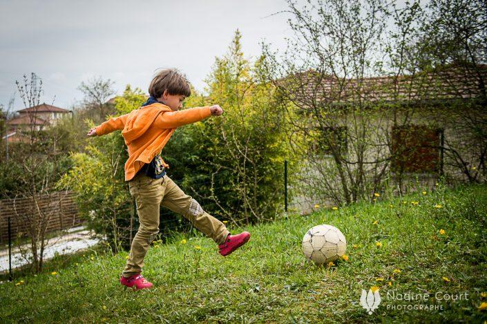 Image d'un enfant jouant au ballon dans son jardin - reportage documentaire de famille