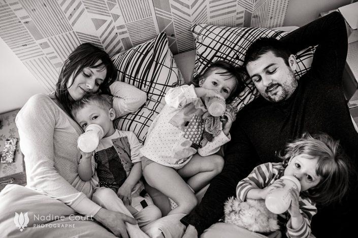 Les enfants boivent le biberon dans le lit de papa et maman - Reportage documentaire famille en Haute Savoie
